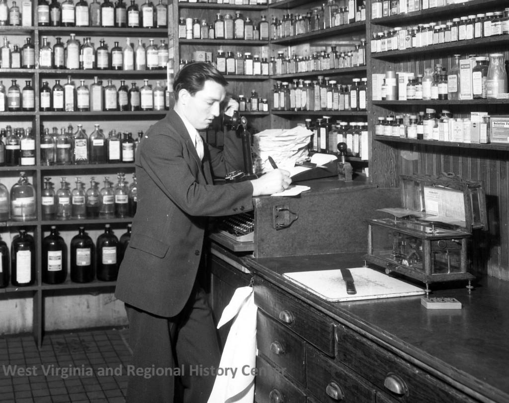 Man at cash register, Camp Drug Company, Prescription Department, Charleston, West Virginia, ca. 1930s