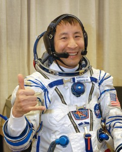 Astronaut Edward T. Lu, Expedition Seven NASA ISS science officer and flight engineer, wearing his Russian Sokol suit, gives a thumbs-up as he waits for a leak check, Soyuz inspection and seat liner check in the Soyuz Integration Facility at the Baikonur Cosmodrome in Kazakhstan. Photo credit: NASA/Bill Ingalls.