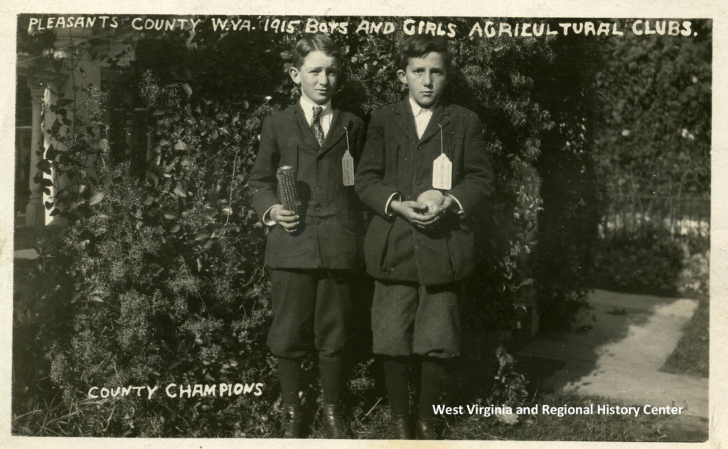 Posed outdoor portrait of two young boys, holding corncob and potato?