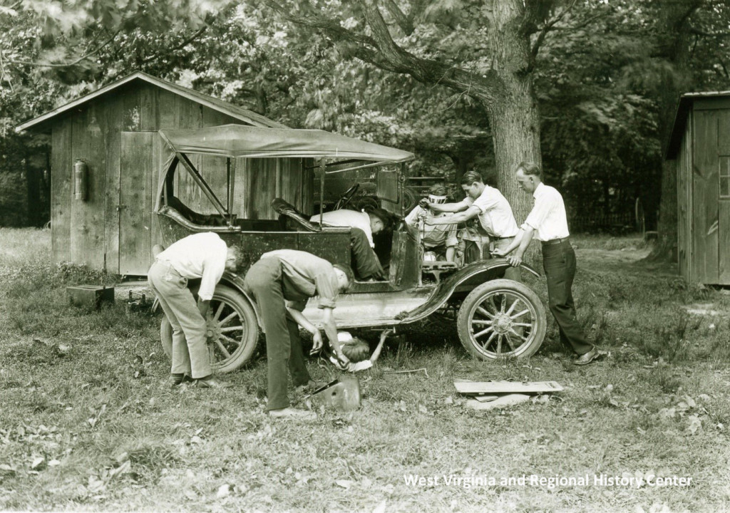 Group of men working to repair and old car