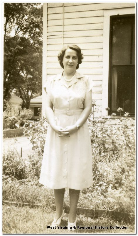Portrait of Katherine Estenline, Director of Scott's Run Methodist Settlement House 1939-1941, standing outside a building near a flower garden.