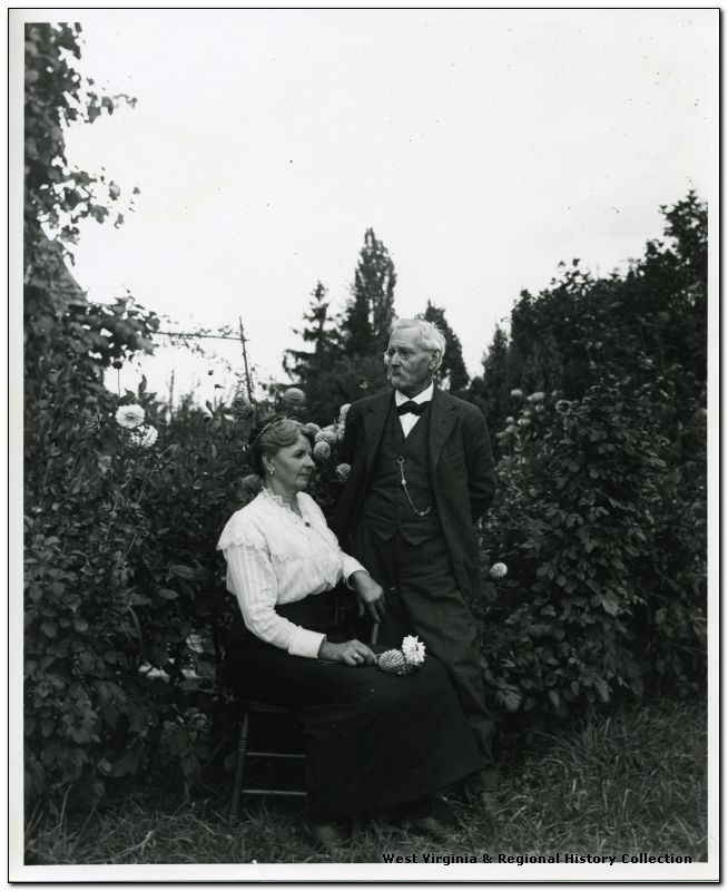 Elka Hassig is sitting near a flower garden while Ernest Hassig stands next to her.