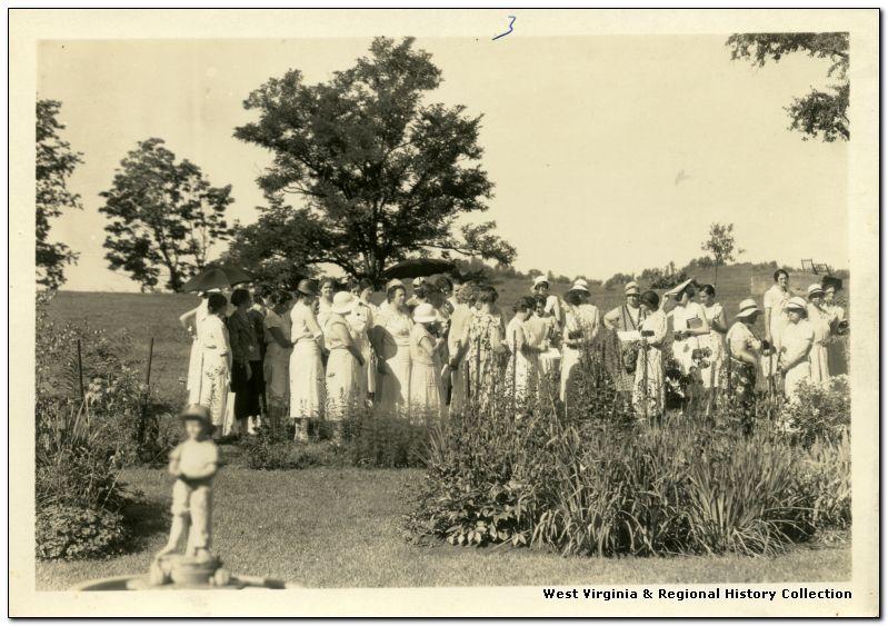 Group of women standing near garden plantings.
