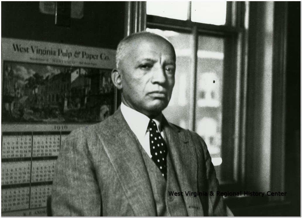 Carter G. Woodson Standing in front of a window