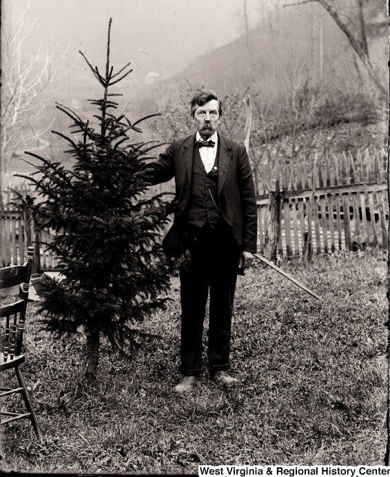 Man in Helvetia, WV, with saw and hand cut Christmas tree