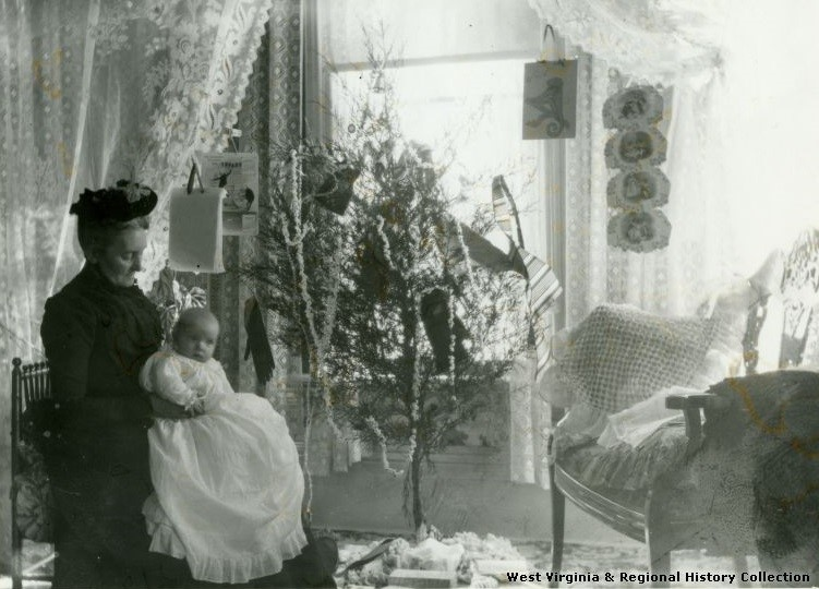 A woman holding a baby, while sitting near a popcorn draped Christmas tree