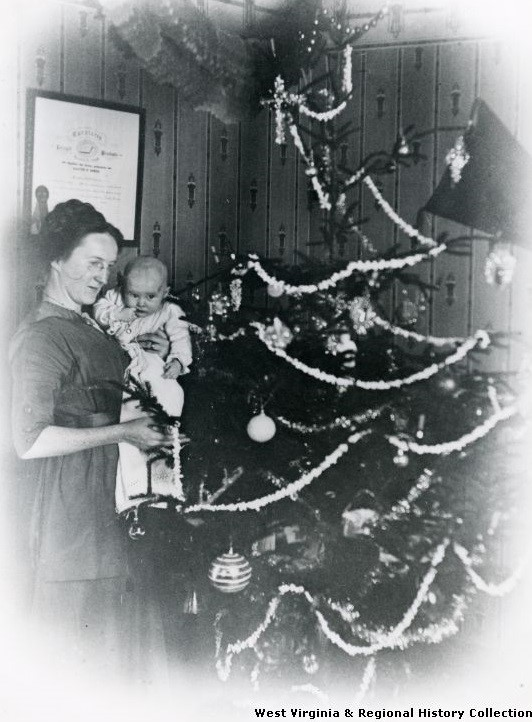 Woman and baby decorating Christmas Tree