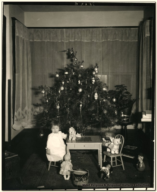 Child and Gifts in front of the Christmas tree