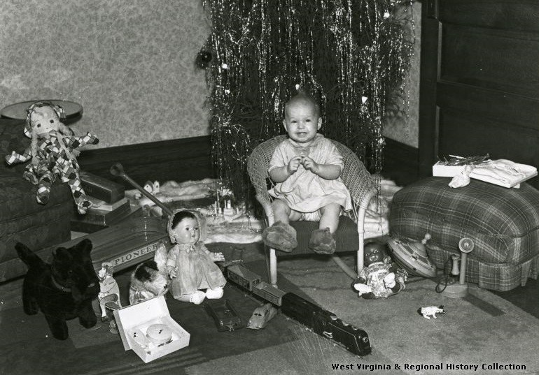 Baby Sits with Toys in Front of a Christmas tree