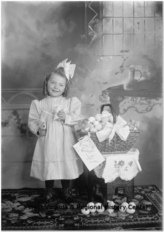Little girl posing next to Easter basket filled with eggs