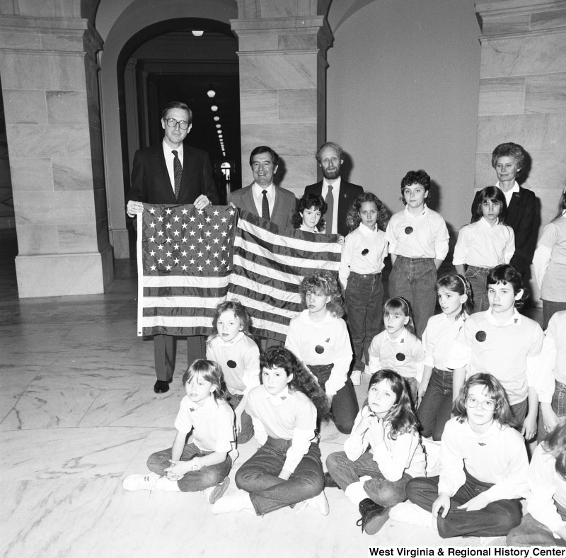 Photograph of Senator Jay Rockefeller (D-WV) and Congressman Nick Rahall (D-WV) pose with a group of young children in the Capitol Rotunda. Senate Photographic Studio, March 20, 1987. From the Senator John D. (Jay) Rockefeller IV papers.