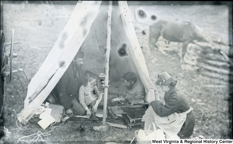 Thomas Biscoe (left) and Walter Biscoe (right) having breakfast in their tent with a child and a woman
