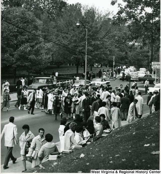 Many students crossing the street in front of Stewart Hall