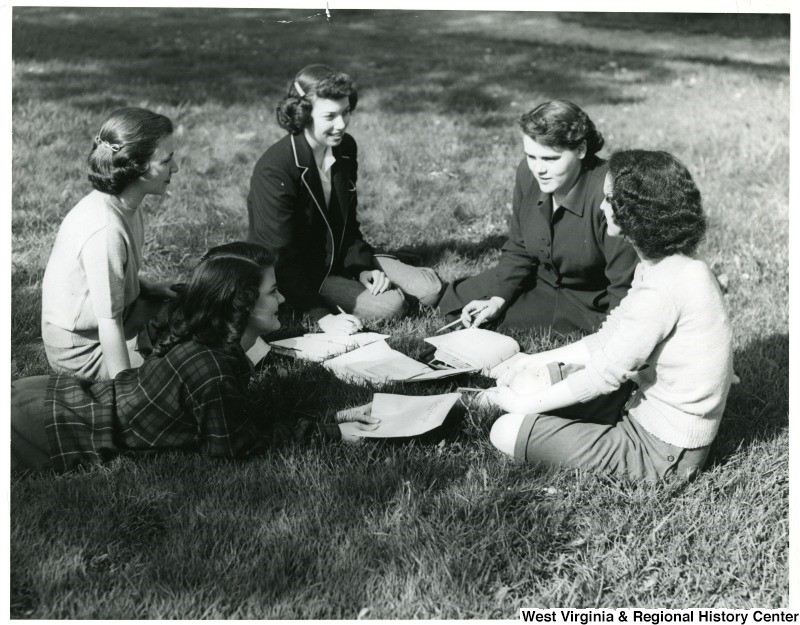 Female student study group on grass outdoors