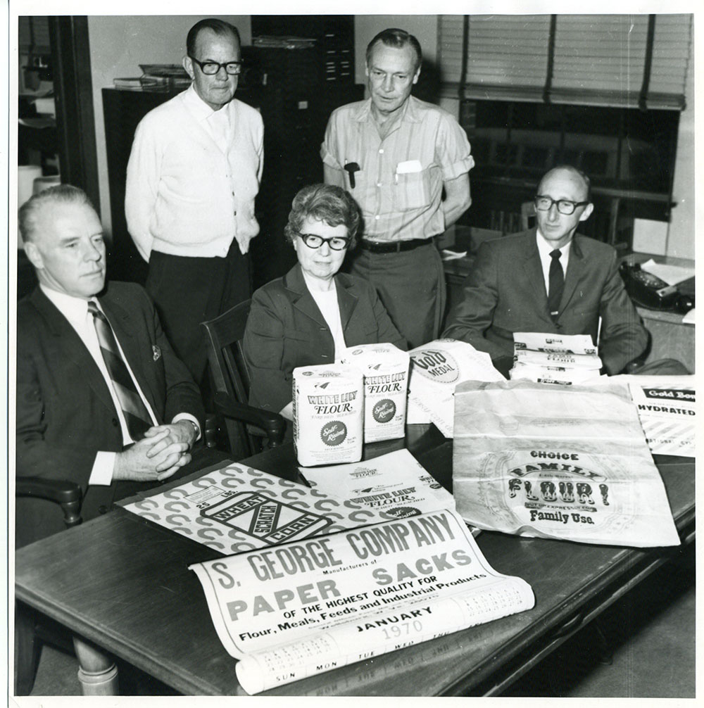 S. George Company employees surrounding a table with paper sack products