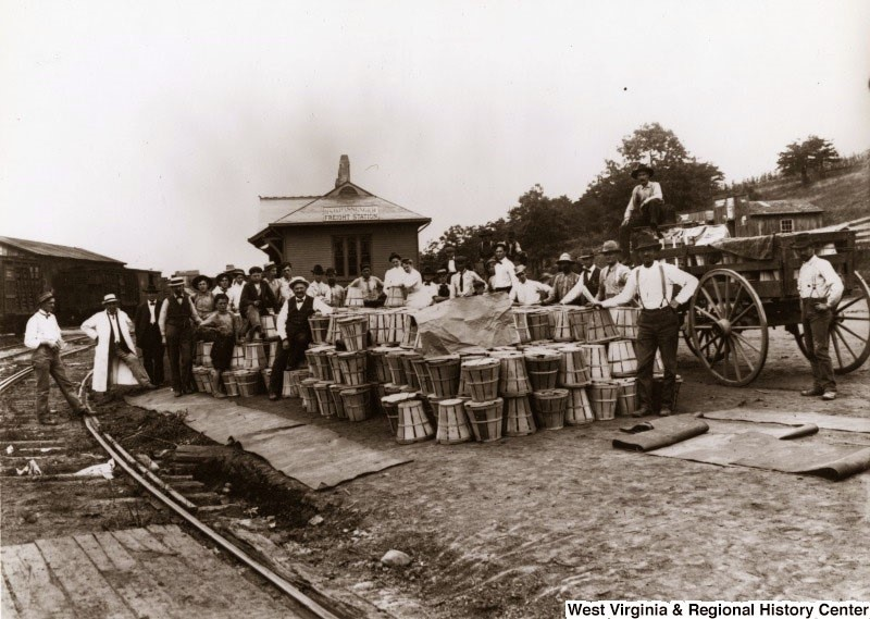 Large group standing at train station with crates of fruit