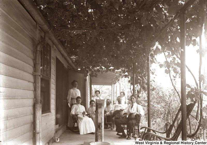 Back porch of a home with 8 family members sitting for a group portrait