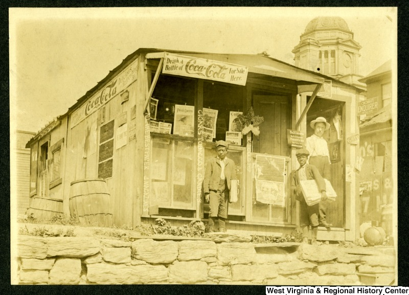 Two African-American Newsboys and Unidentified man stand outside C. N Chilins Newsstand
