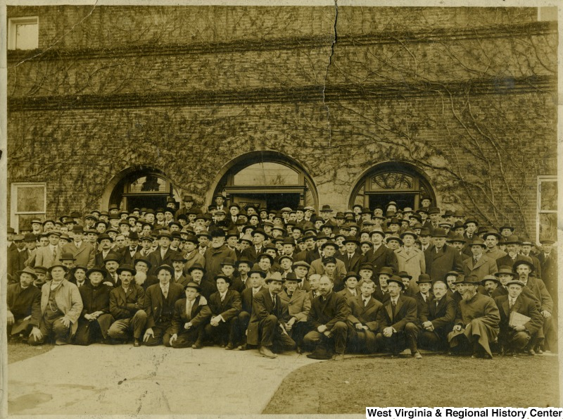 Group portrait of men in front of building