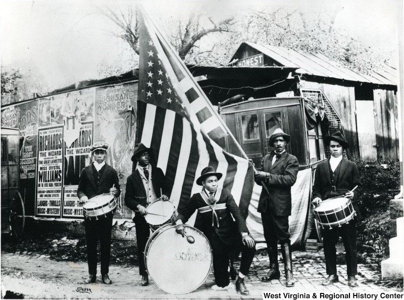 Five African American drum corps members with drums and flag