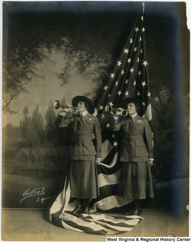 Two YWCA women pose with bugles and flag