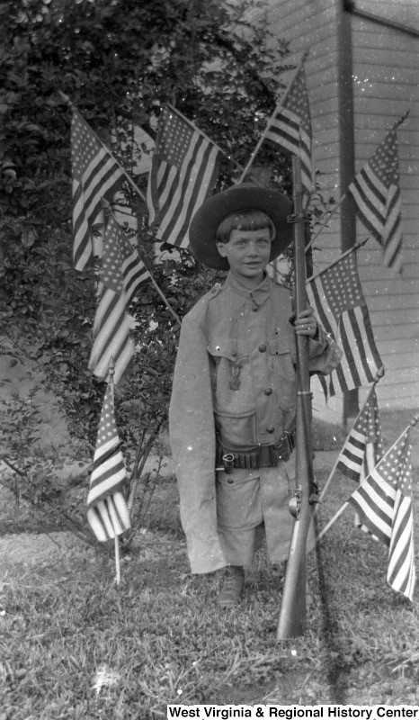 9-year-old James Edwin Green, Jr. posing in his father's Spanish American War uniform while holding a rifle, surrounded by American flags