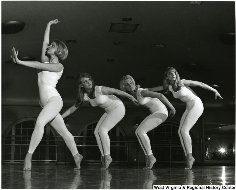 Four WVU Orchesis dancers in white costumes
