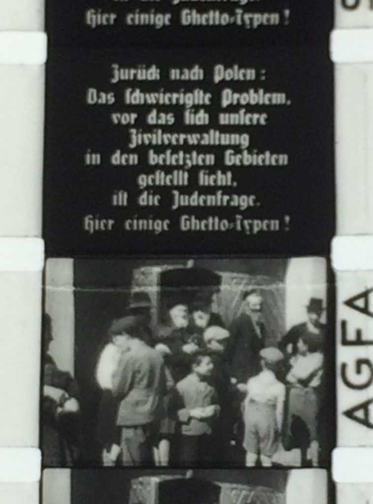 Film strip showing a frame of text in German above an image of presumably Polish Jews