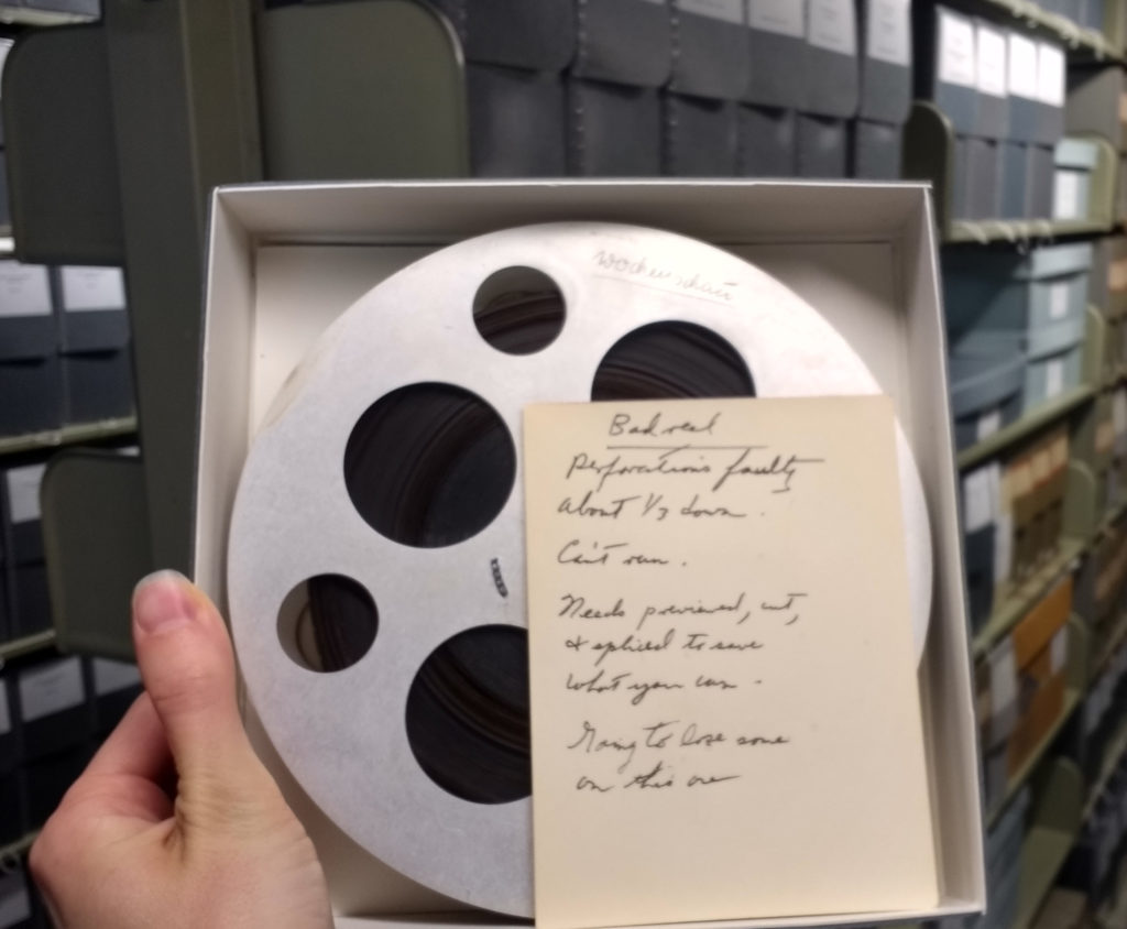 Reel of film with a note beside it