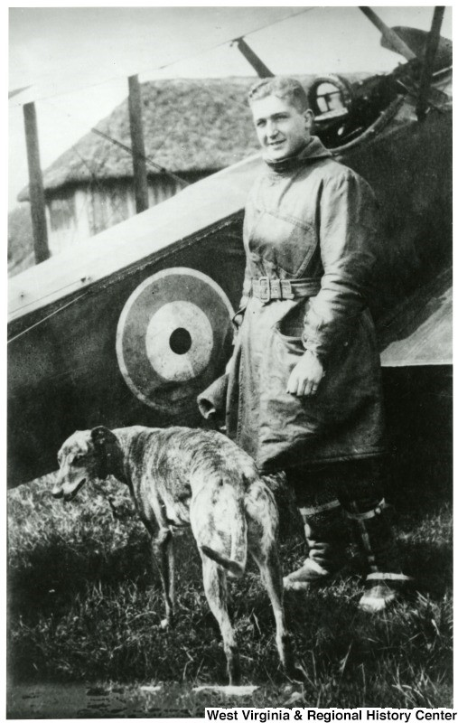 Lt. Louis Bennett, Jr. and his dog standing in front of a SE5a biplane