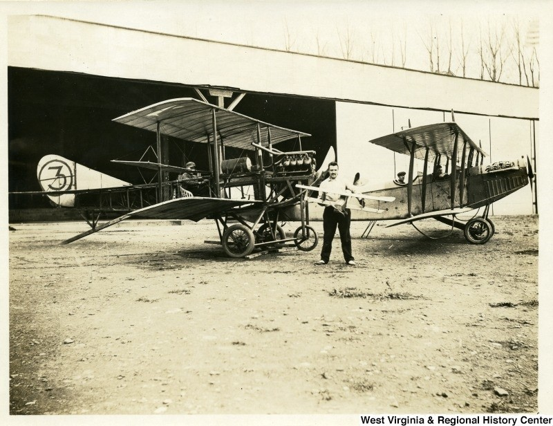 Man holding model biplane, standing in front of two real biplanes