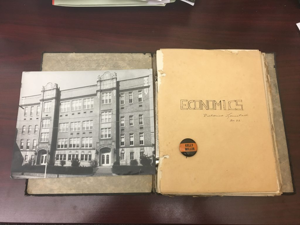 Photograph of Kelly Miller High School, economics notebook, and Kelly Miller pin