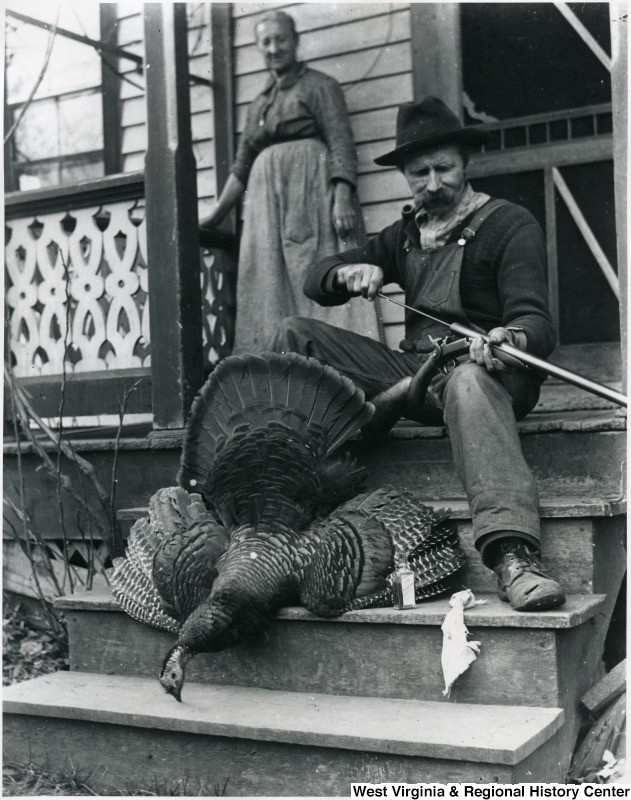 Gottfried Aegerter cleaning his gun, with dead turkey on steps in front of him