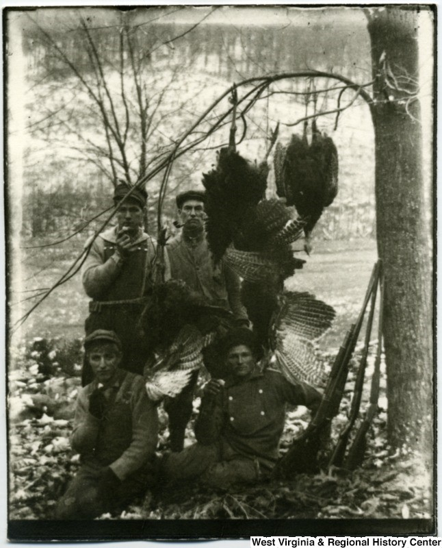 Four hunters displaying the turkeys they caught