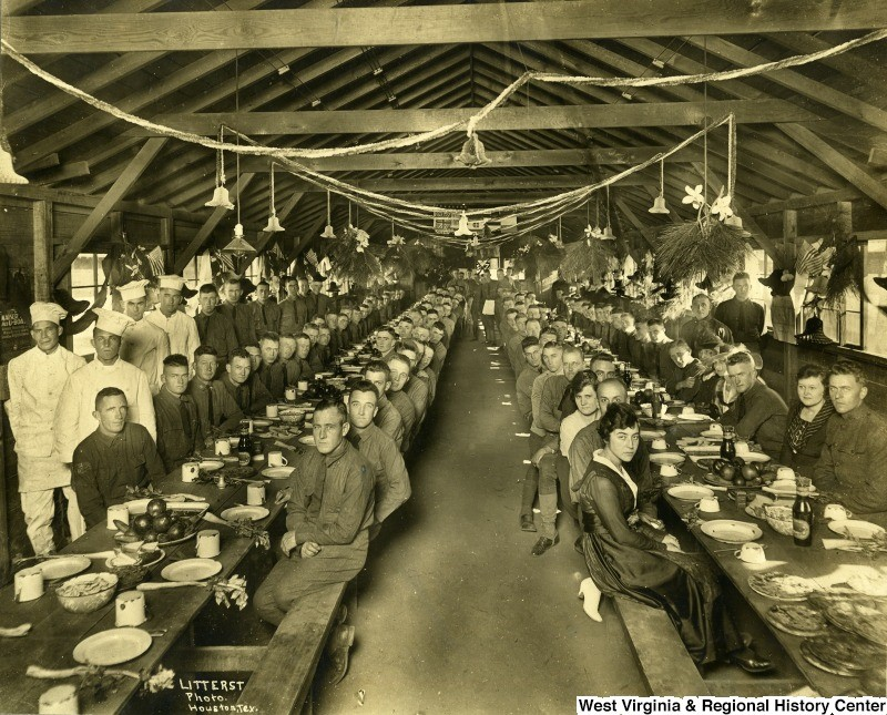 Thanksgiving dinner at Camp Logan, 1918, with men and women seated at long tables