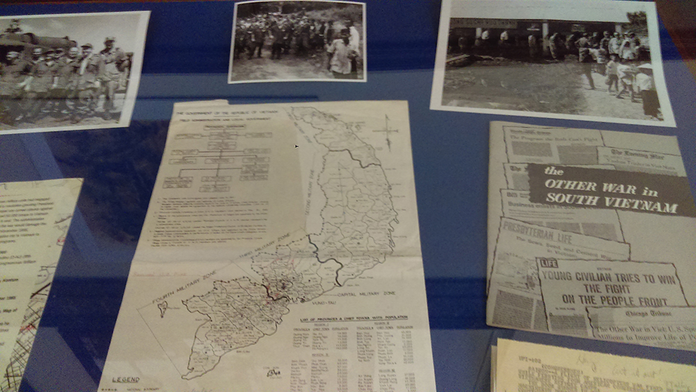 Display case containing maps, photos, and printed material related to the Vietnam War