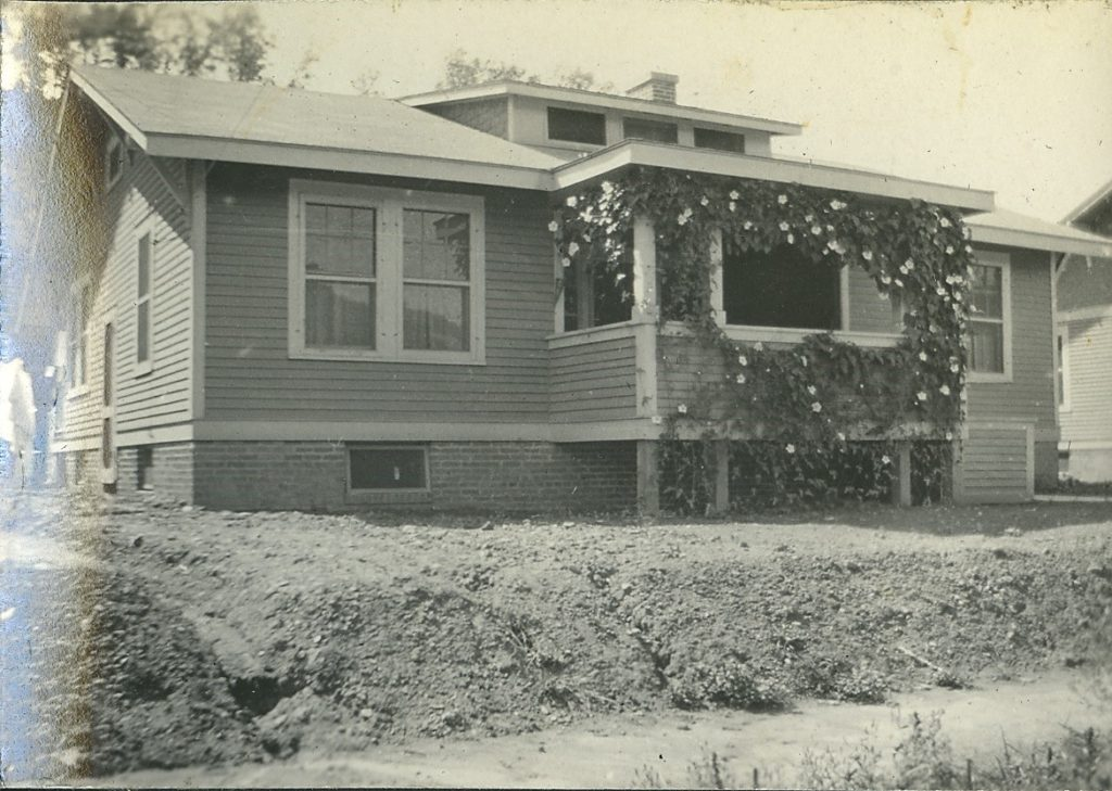 Minter home in Nitro, with flowers on porch and a dirt front yard