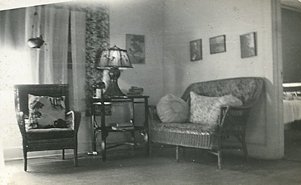 Interior of Minter home in Nitro, showing wicker chair and loveseat