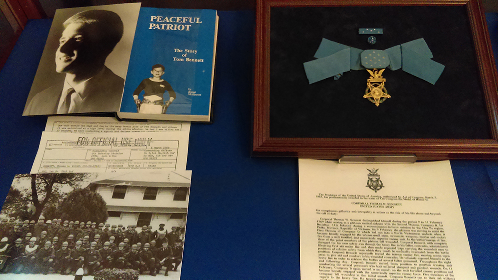 Display case that includes Tom Bennett's posthumous Medal of Honor next to a book about him