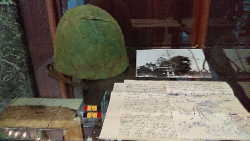 Display case containing Paul Casto's military uniform helmet, among other items.