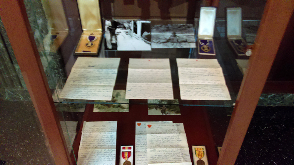 Display case containing letters and Vietnam War medals