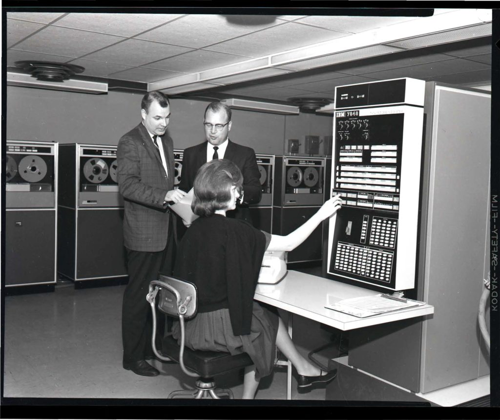 Two men standing, one woman operating the control panel of an IBM 7040 at WVU