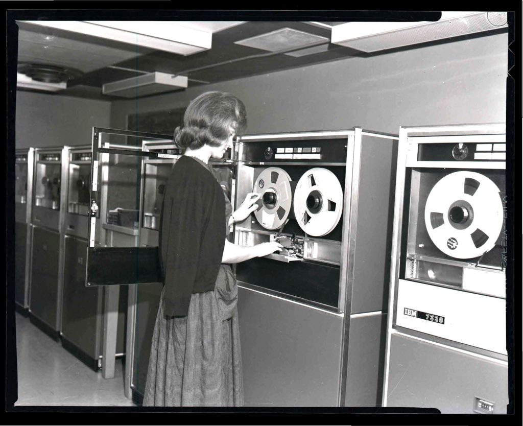 Woman working with IBM 7330 data tape storage units at WVU