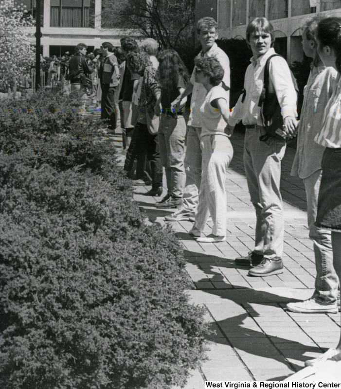 Students on WVU campus holding hands as part of a protest
