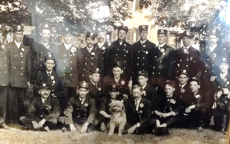 Group photo of Morgantown Firemen, outside, with dog in center