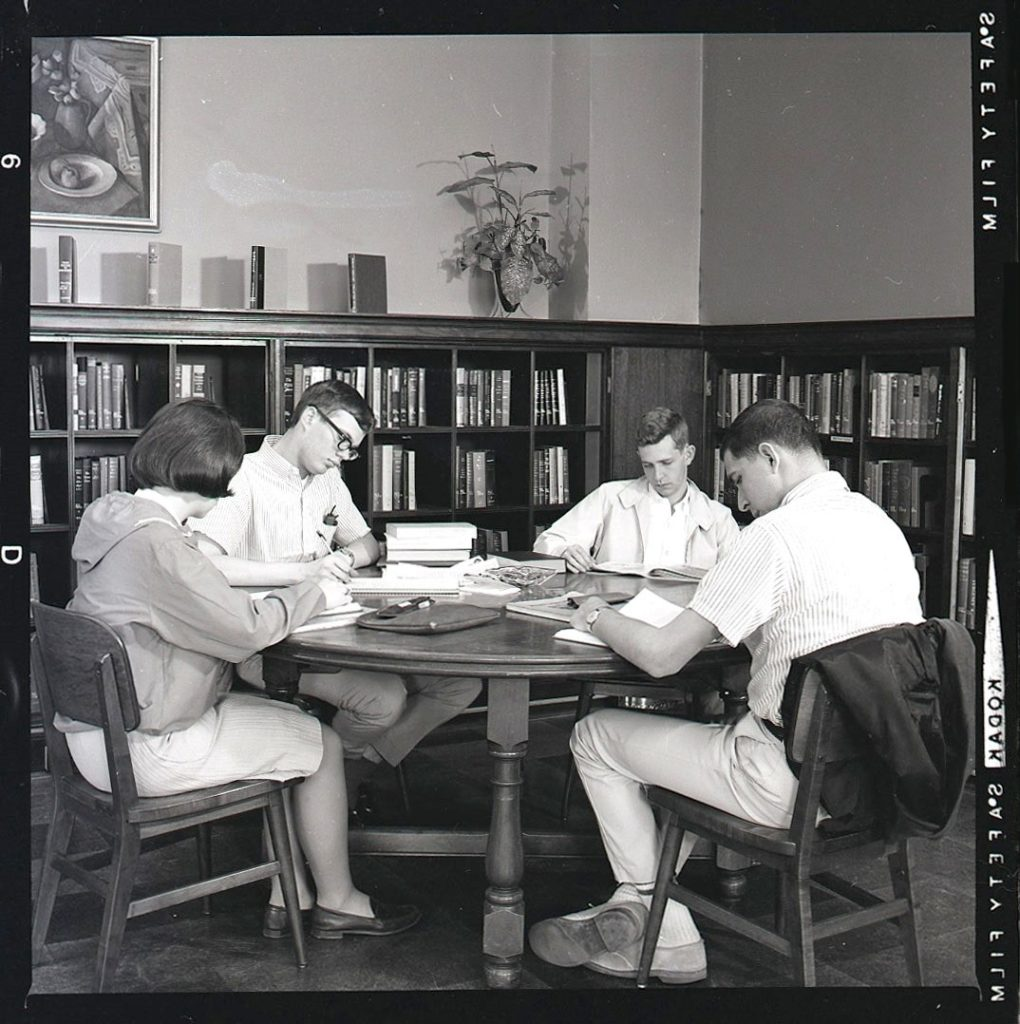 Four students studying at a table in corner of reading room, Wise Library, May 1965