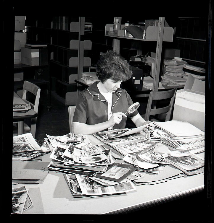 Librarian or student worker using magnifying glass to study pile of photos at the West Virginia and Regional History Center, Wise Library, May 1967
