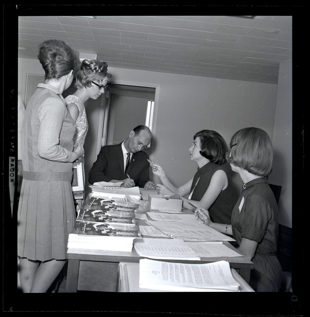 Students and staff gathered at a desk during the opening day of Towers residence halls, 1965