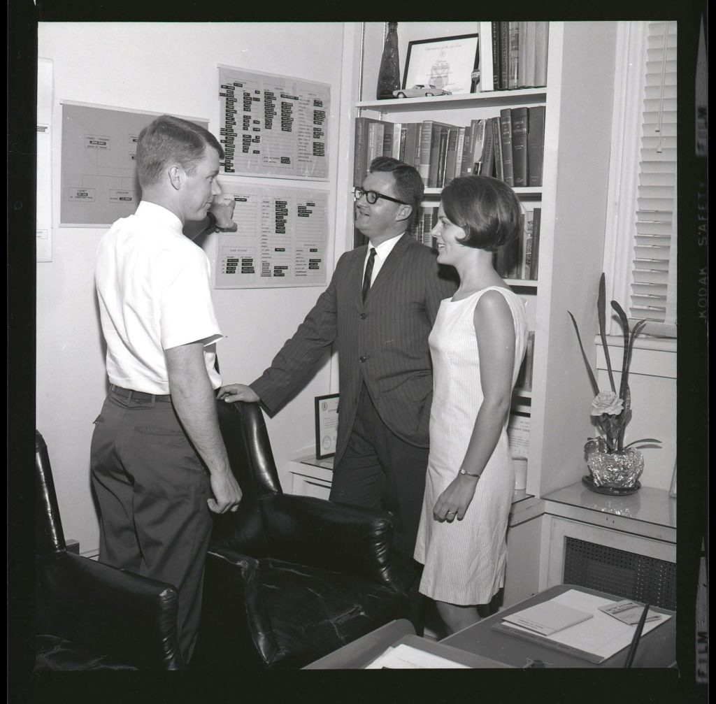 Mr. James Watkins (center), standing with two other people, 1967
