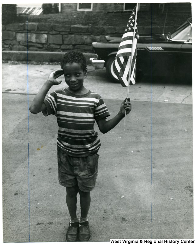 African-American boy saluting and holding an American flag